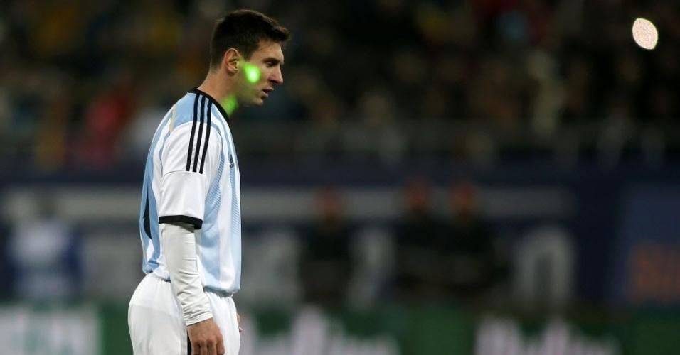 05.mar.2014 - Torcedores miram laser no rosto de Messi durante amistoso entre Argentina e Romênia, em Bucareste