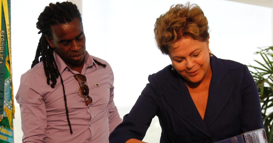 13.mar.2014 - A presidente Dilma Rousseff (d) recebeu nesta quinta-feira em Brasília o árbitro gaúcho Marcio Chagas e o volante Tinga (e) para discutir o racismo no futebol. Marcio e Tinga foram recentemente alvos de ofensas racistas durante partidas. No encontro, Dilma recebeu uma camisa do Cruzeiro, time pelo qual Tinga joga atualmente