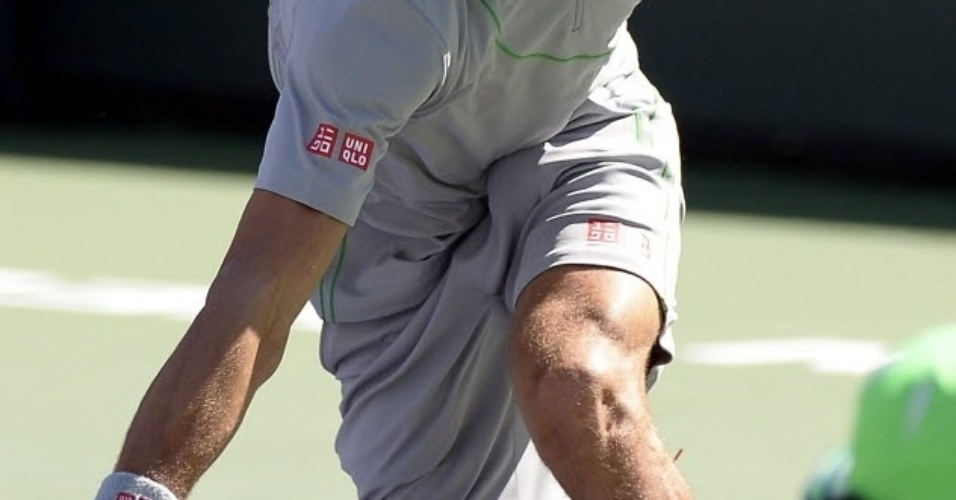 14.mar.2014 - Novak Djokovic se abaixa para buscar bola na partida contra Julien Benneteau