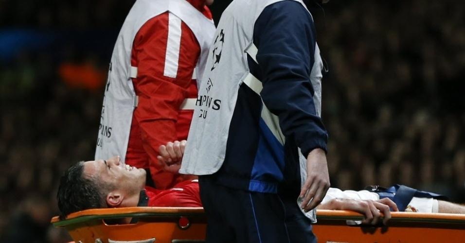 19.mar.2014 - Robin van Persie deixa o gramado do Old Trafford de maca com dores na panturrilha após dividida no jogo entre Manchester United e Olympiakos