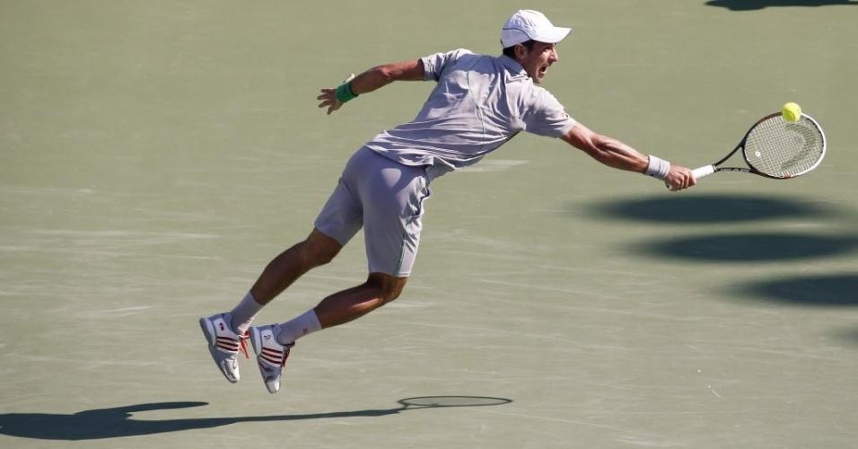 21.mar.2014 - Novak Djokovic se estica para salvar golpe, com o backhand, no duelo contra Jeremy Chardy em Miami
