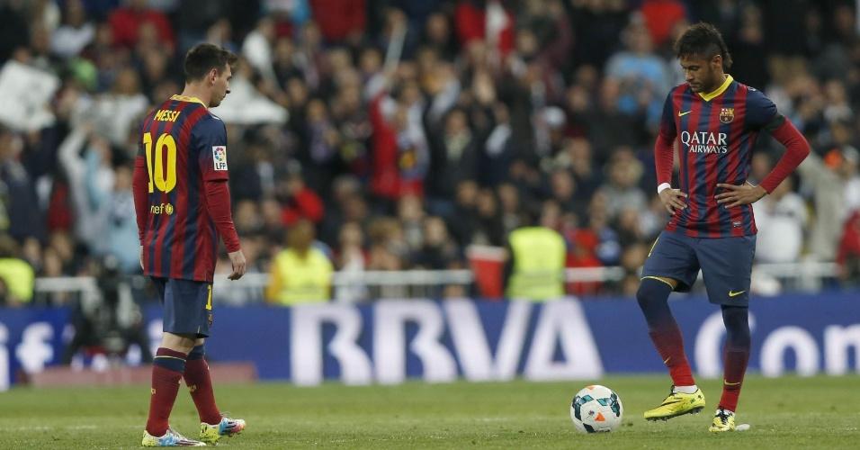 23.mar.2014 - Cabisbaixos, Messi (e) e Neymar aguardam sinal do árbitro para reiniciar a partida após um gol do Real Madrid contra o Barcelona no clássico deste domingo pelo Campeonato Espanhol