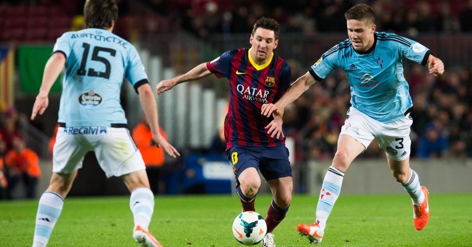 26.mar.2014 - Messi parte para o ataque e dribla jogadores do Celta na durante jogo válido pelo Campeonato Espanhol