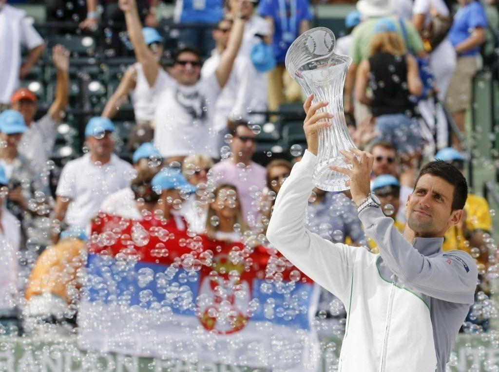 30.mar.2014 - Com a bandeira da Sérvia ao fundo, Novak Djokovic levanta o troféu do Masters 1000 de Miami