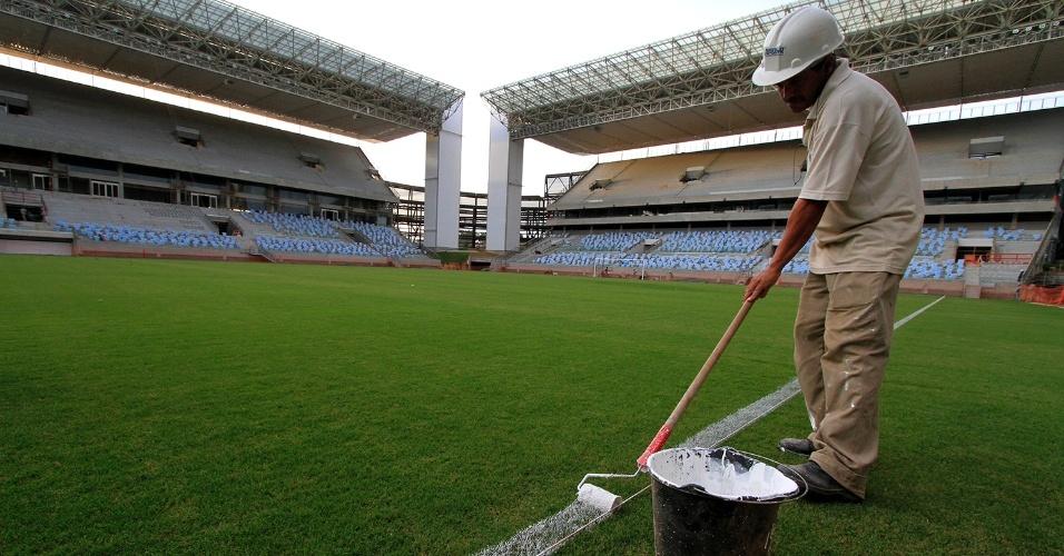 31.mar.2014 - Funcionário faz a demarcação no gramado da Arena Pantanal, que terá sua primeira partida oficial nesta quarta-feira, entre Mixto x Santos pela Copa do Brasil