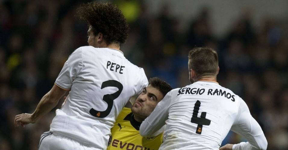 02.abr.2014 - Pepe e Sergio Ramos fazem sanduíche em Sokratis, do Borussia Dortmund, durante duelo das quartas de final da Liga dos Campeões