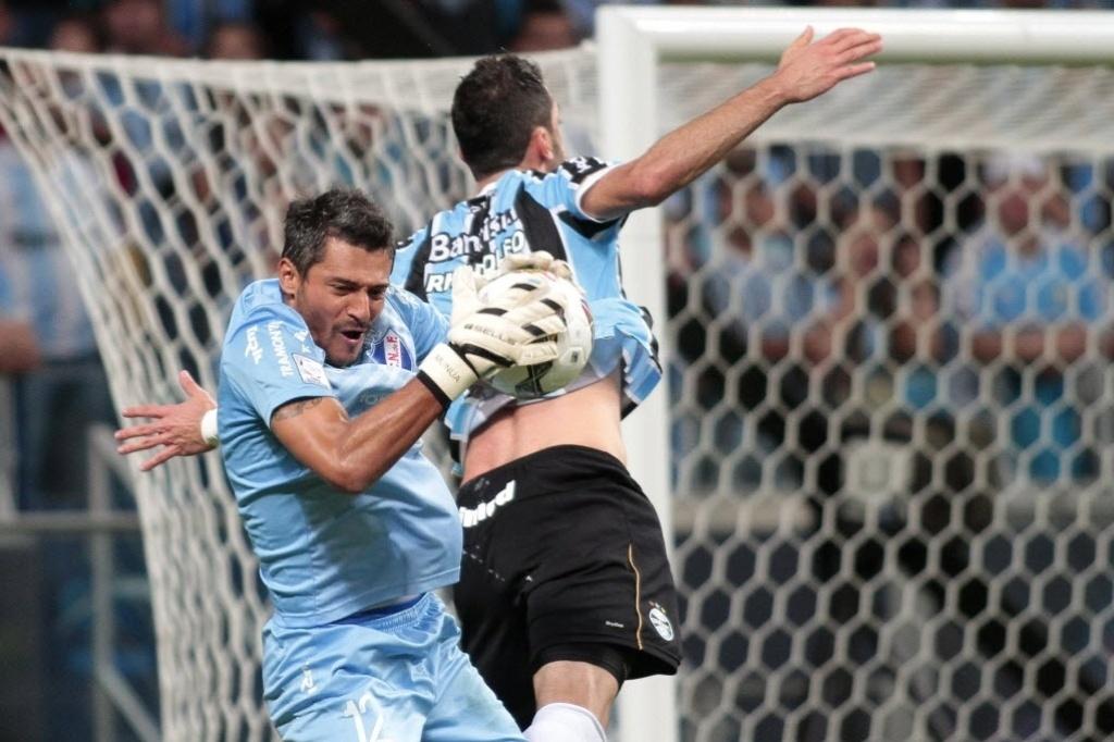 10.abr.2014 - Goleiro Munúa, do Nacional, leva a melhor sobre o zagueiro Rhodolfo, do Grêmio, pela Libertadores