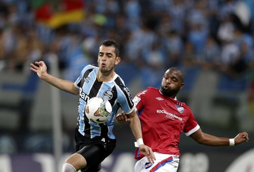 10.abr.2014 - Rhodolfo se antecipa a Santiago García no jogo entre Grêmio e Nacional, pela Libertadores