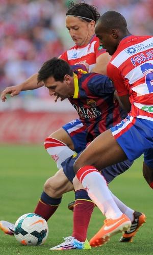 12.abr.2014 - Messi tenta escapar da forte marcação de dois jogadores do Granada durante partida pelo Campeonato Espanhol