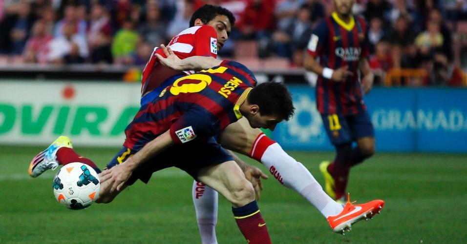 12.abr.2014 - Messi tropeça após disputa de bola com Tiago Ilori durante partida entre Barcelona e Granada