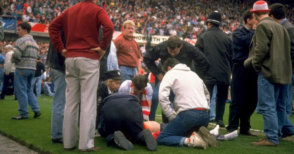 15.04.89 - 15.04.89 - Pessoas são atendidas no gramado durante a tragédia de Hillsborough, há 25 anos; 96 torcedores do Liverpool foram mortos pisoteados e presos ao alambrado no superlotado estádio de Hillsborough, em Sheffield, em um jogo contra o Nottingham Forest pela Copa da Inglaterra