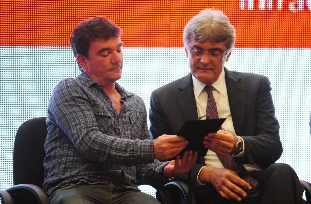 15.abr.2014 - Andrés Sanchéz observa documento de posse do Itaquerão que foi entregue ao Corinthians pela Odebrecht