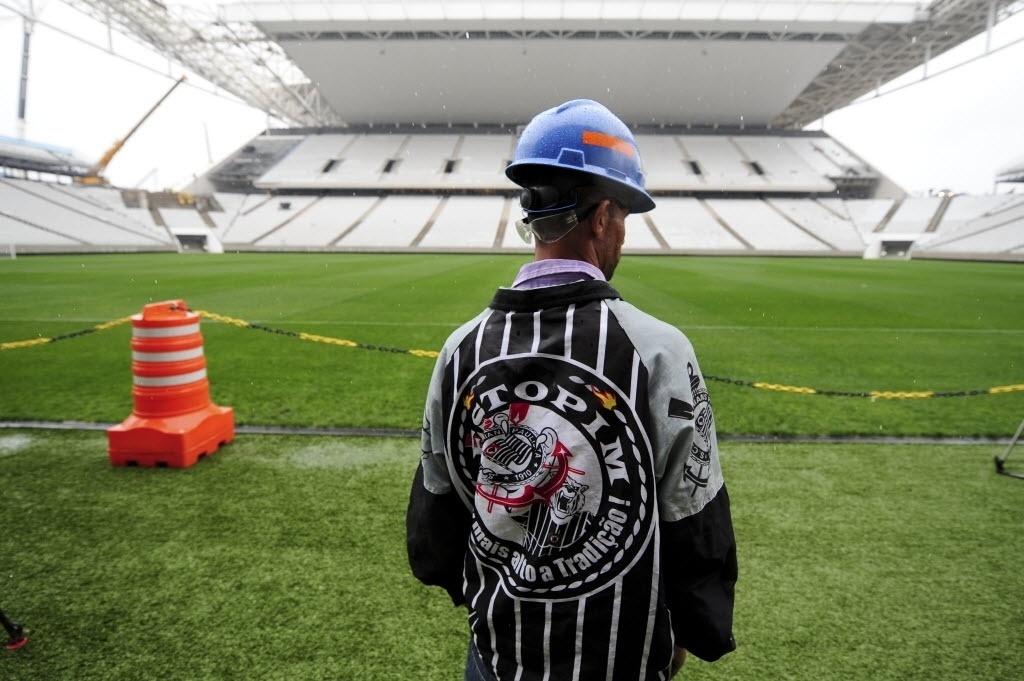 15.abr.2014 - Corintiano, operário do Itaquerão observa gramado do estádio que foi entregue ao clube paulista nesta terça-feira (15/04)