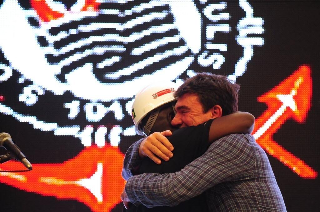 15.abr.2014 - Ex-presidente do Corinthians, Andrés Sanchez abraça operário do Itaquerão na cerimônia de entrega de posse do estádio ao clube paulista