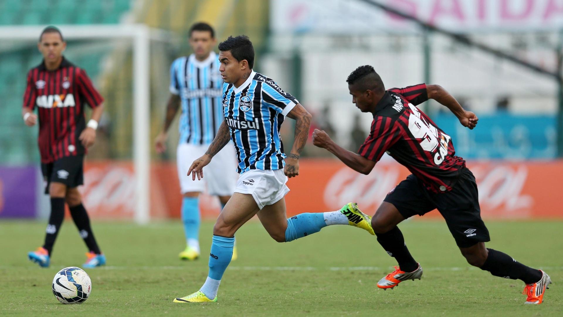 20.abr.2014 - Dudu, do Grêmio, conduz a bola perseguido por Mario Sergio, do Atlético-PR