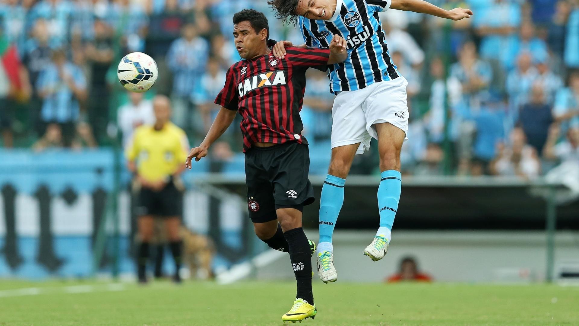 20.abr.2014 - Ederson, do Atlético-PR, e Geromel, do Grêmio, disputam bola aérea