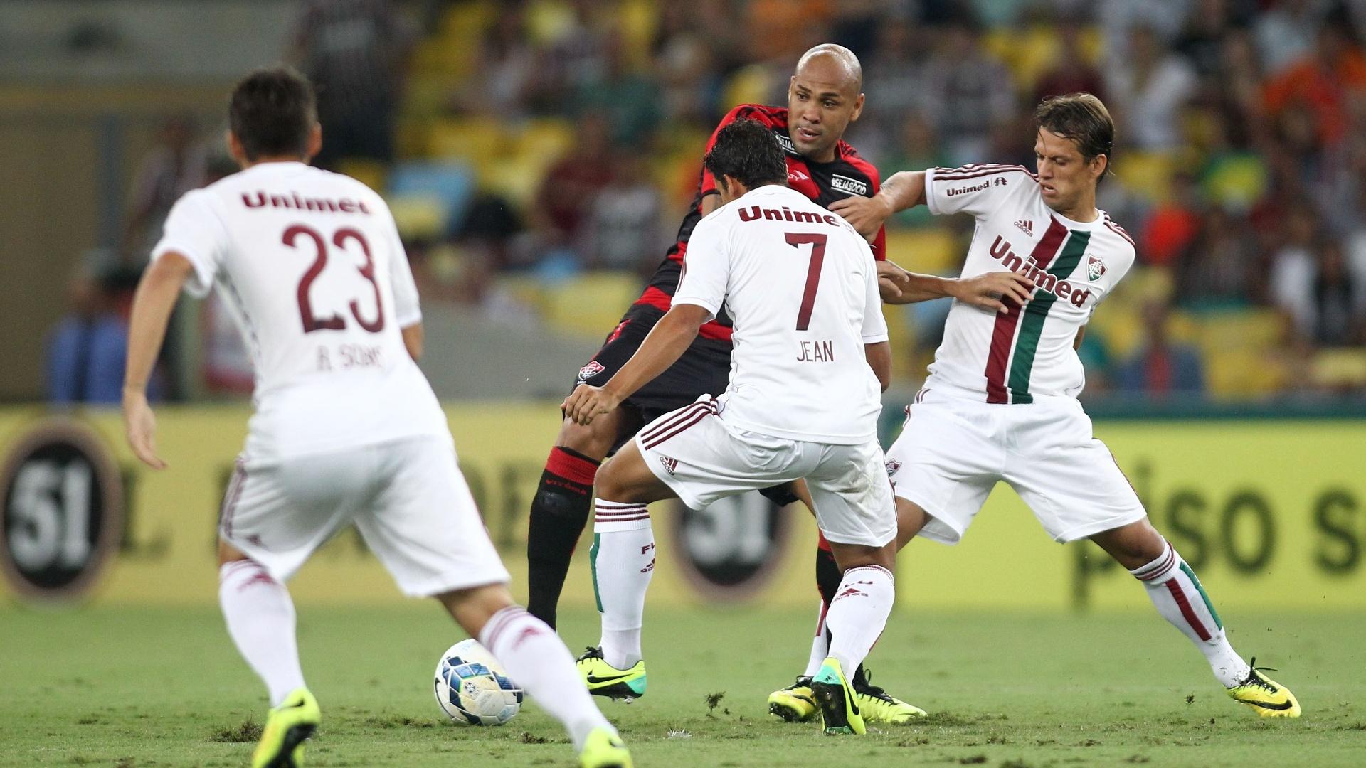 3.mai.2014 - Atacante Souza é cercado por dois marcadores do Fluminense durante duelo no Maracanã