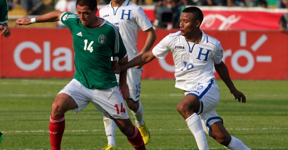 22.mar.2013 - Luis Garrido (d), de Honduras, tenta conter o avanço do mexicano Javier 'Chicharito' Hernández durante partida pelas eliminatórias da Copa do Mundo-2014