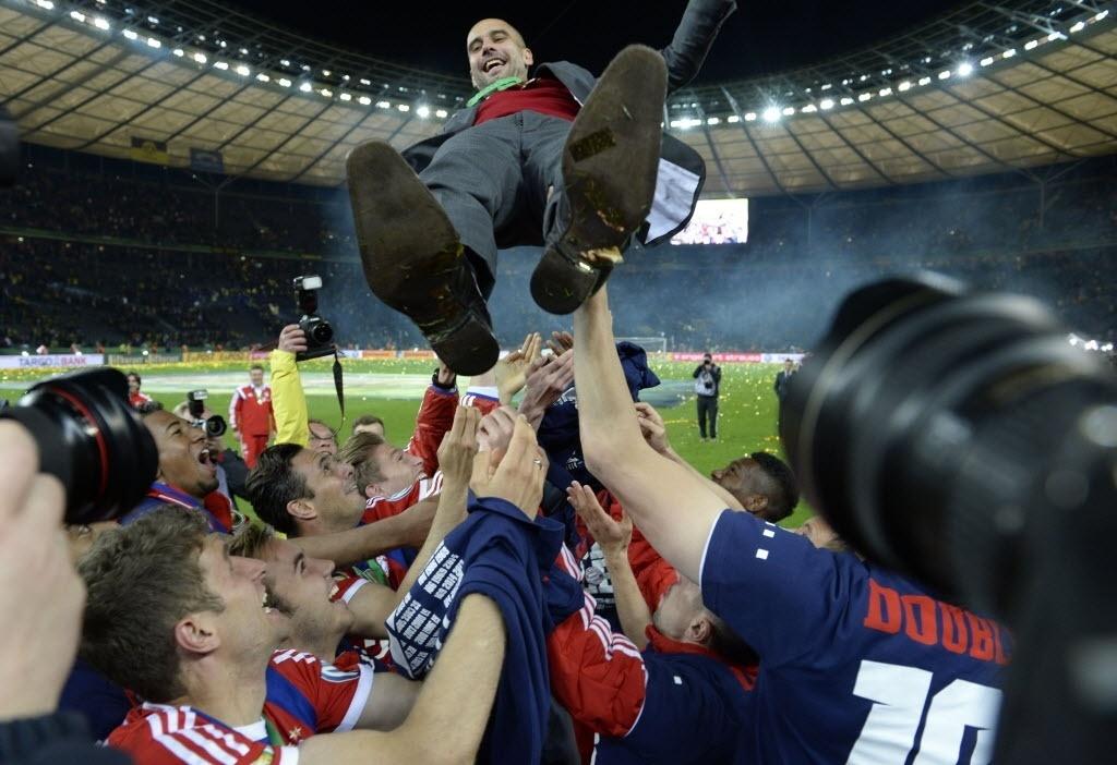 Jogadores do Bayern de Munique jogam Guardiola para cima depois do título contra o Dortmund