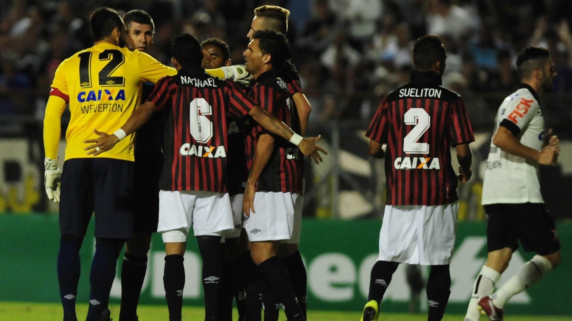 21.mai.2014 - Jogadores do Atlético-PR questionam árbitro após pênalti marcado para o Corinthians