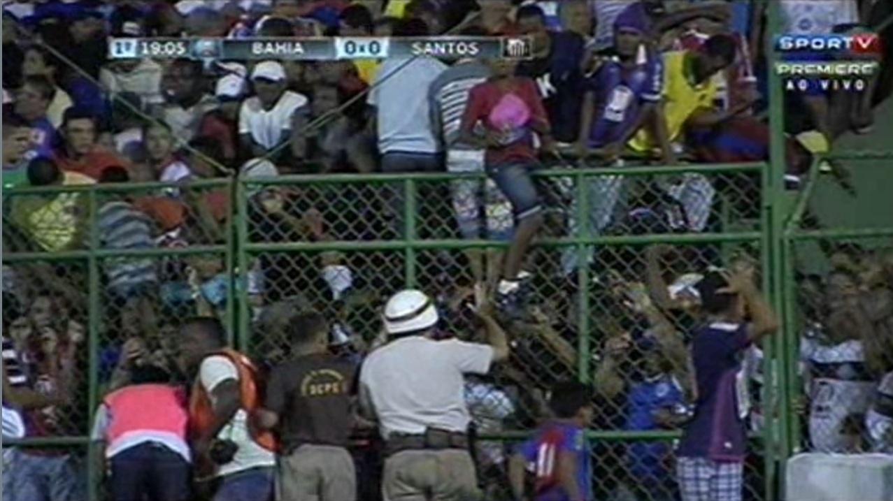 Torcedores tentam passar por cima da grade para sair da lotação nas arquibancadas do jogo entre Bahia e Santos