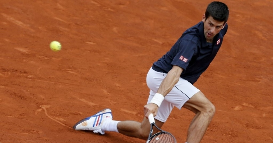 Novak Djokovic desliza para chegar na bola durante partida contra Milos Raonic