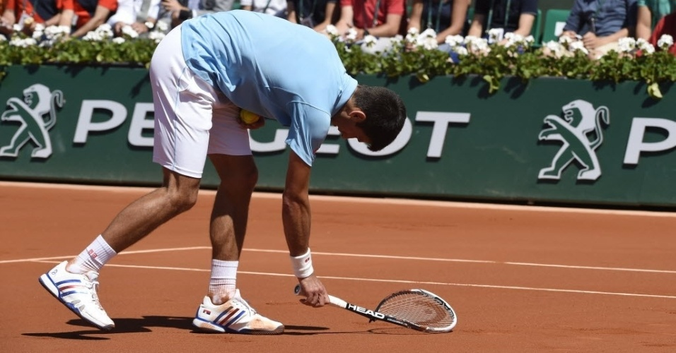 06.jun.2014 - Irritado com erro, Djokovic bate com a raquete na quadra durante jogo contra Ernests Gulbis em Roland Garros