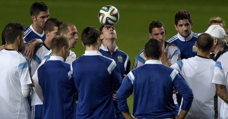 12.jun.2014 - Lionel Messi brinca com a bola enquanto enquanto o técnico Alejandro Sabella conversa com os jogadores da Argentina