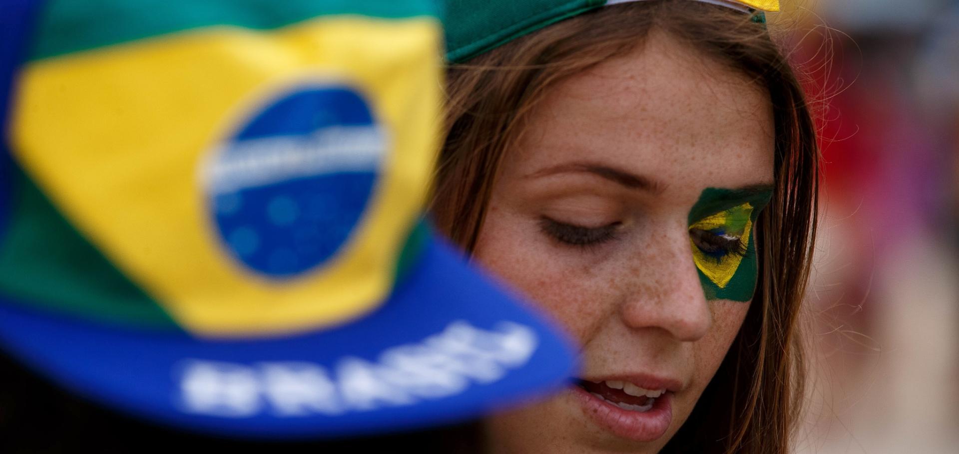 12.jun.2014 - Torcedora marca presença no Itaquerão para Brasil x Croácia, na abertura da Copa do Mundo, com direito a bandeira pintada em torno do olho