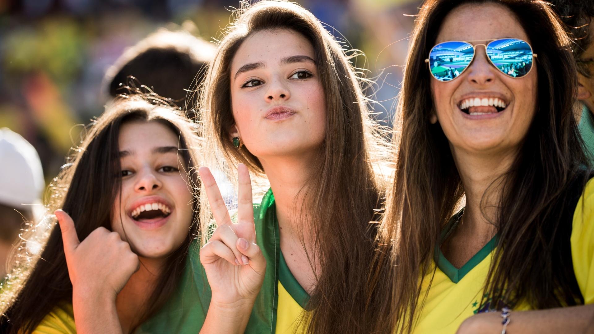 12.jun.2014 - Trio de torcedoras posa para foto na arquibancada do Itaquerão, antes de Brasil x Croácia