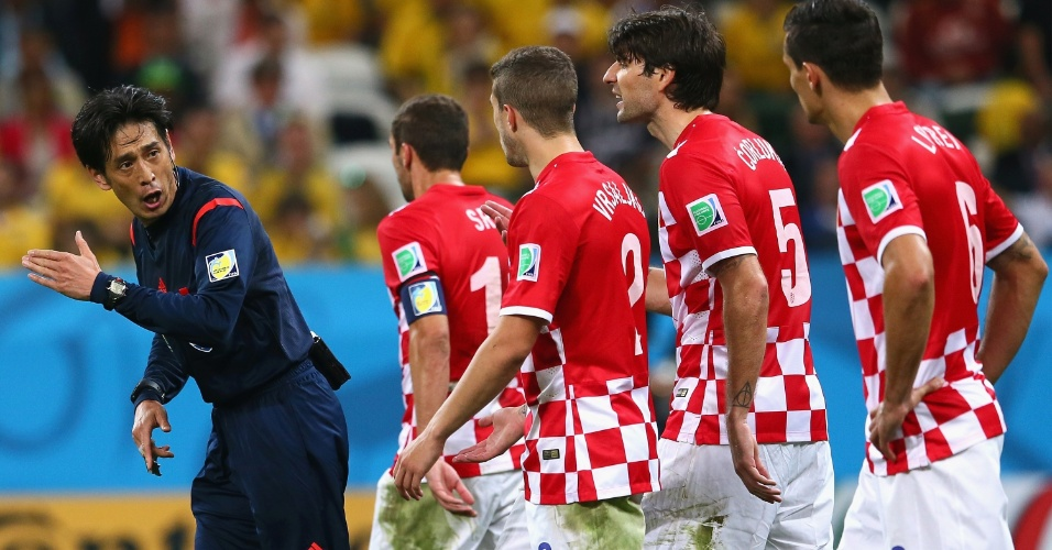 12.jun.2014 - Jogadores da Croácia reclamam com o árbitro Yuichi Nishimura, após pênalti a favor do Brasil