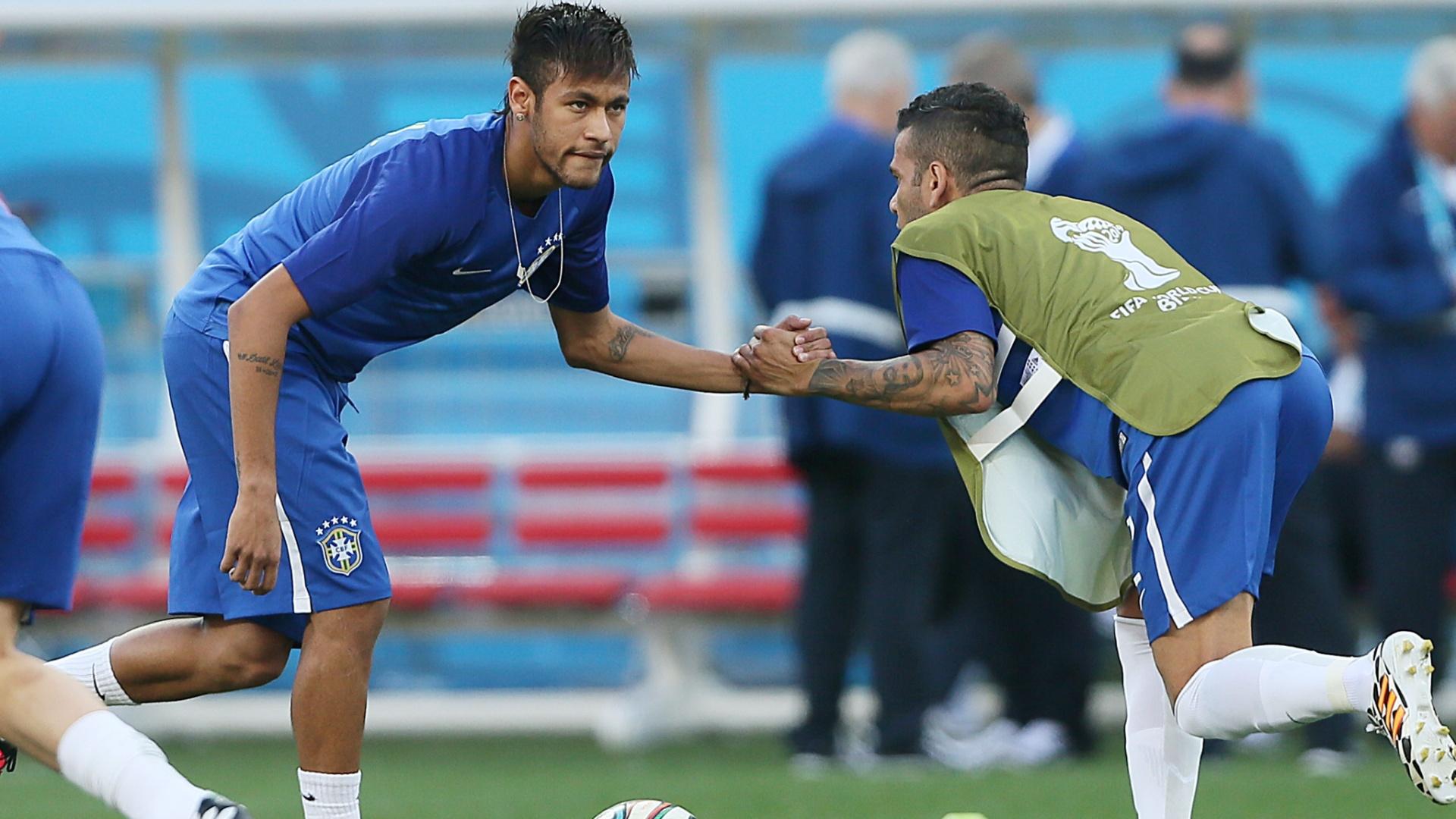 12.jun.2014 - Neymar e Daniel Alves fazem aquecimento no gramado do Itaquerão antes da estreia contra a Croácia