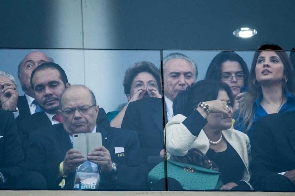 12.jun.2014 - Presidente Dilma Rousseff aguarda início da partida entre Brasil e Croácia e faz sinal de figa no Itaquerão