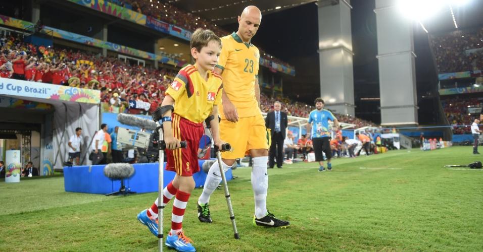 13.jun.2014 - Australiano Mark Bresciano entra no gramado da Arena Pantanal acompanhado de uma criança com deficiência física