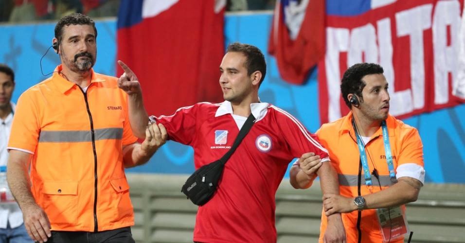 13.jun.2014 - Seguranças barram torcedor que tentou invadir o gramado no final da partida entre Chile e Austrália, na Arena Pantanal