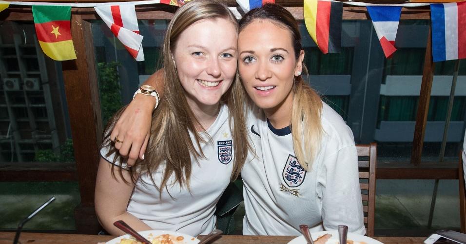 14.jun.2014 - Entre uma mastigada e outra, torcedoras inglesas acompanham juntas à partida da Inglaterra, direto de Hong Kong