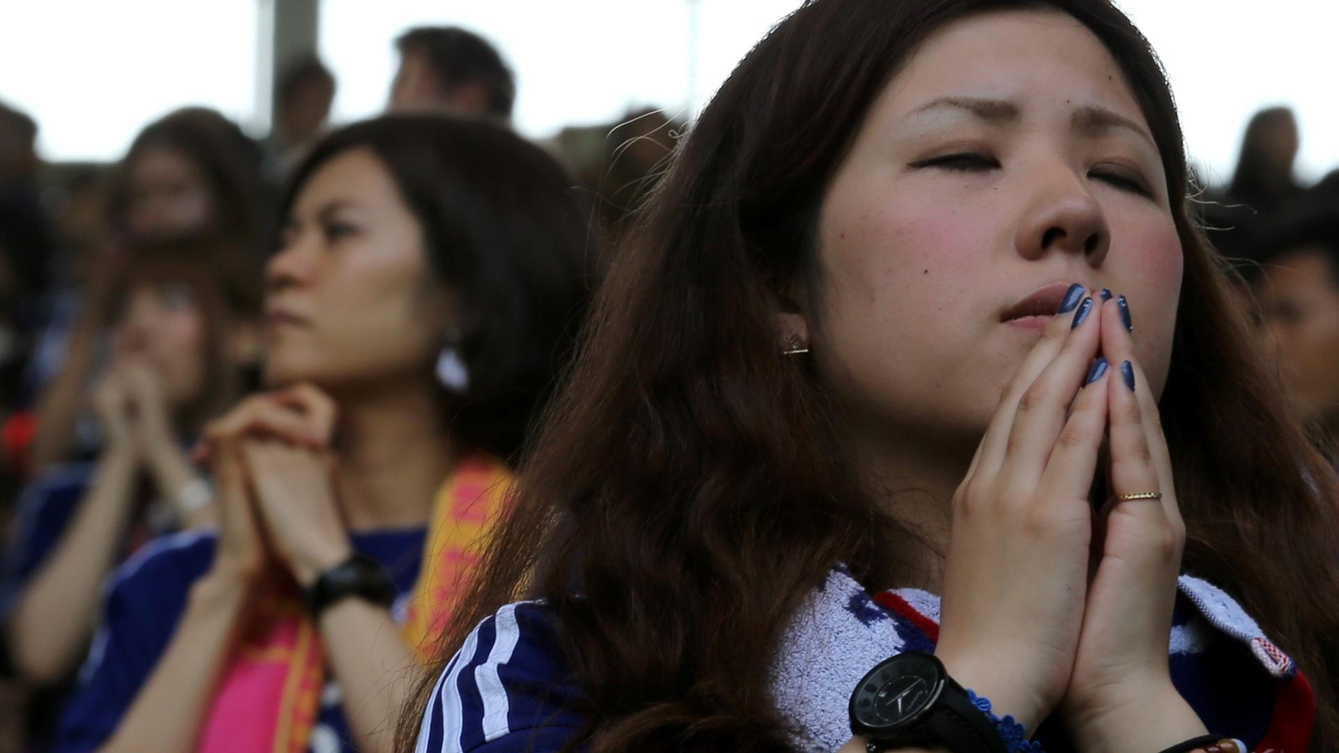 14.jun.2014 - Torcedora se reúne com outros japoneses e acompanha a derrota do Japão, em um telão na cidade de Kove