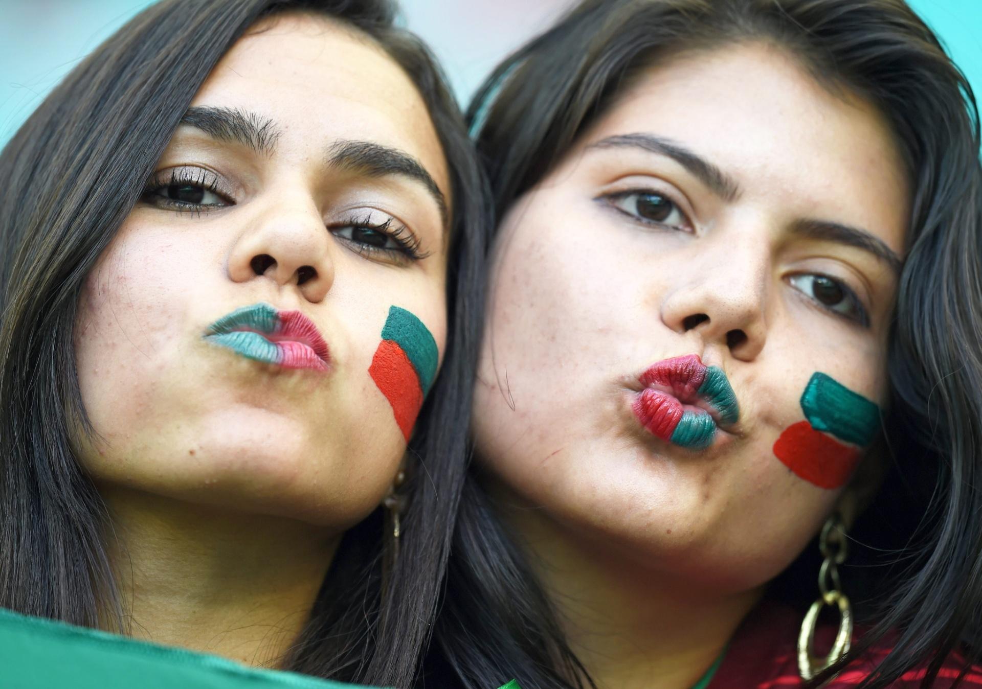16.jun.2014 - Torcedoras pintam o rosto nas cores de Portugal
