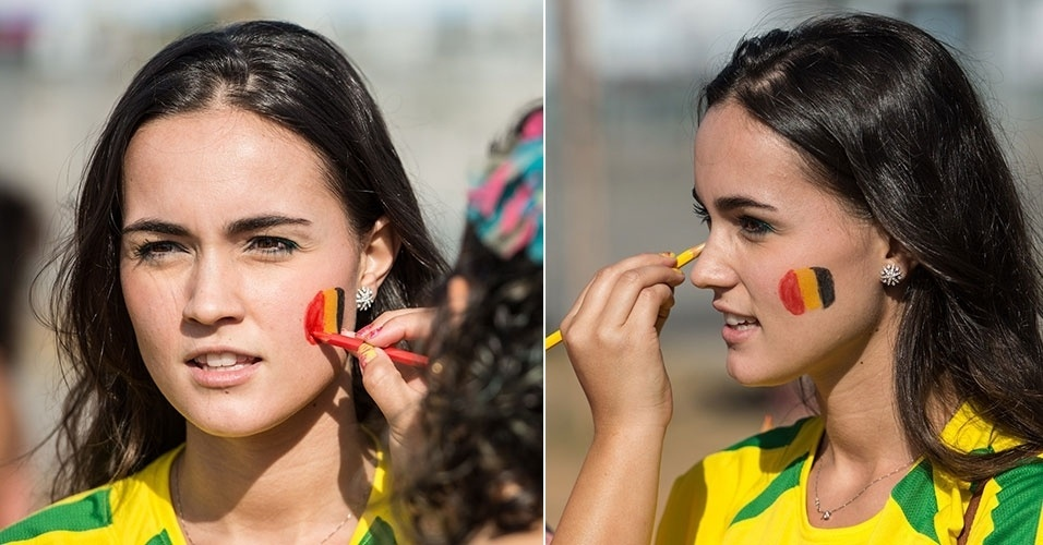 17.jun.2014 - Bela torcedora com a camiseta do Brasil pinta o rosto com as cores da Bélgica para o duelo com a Argélia