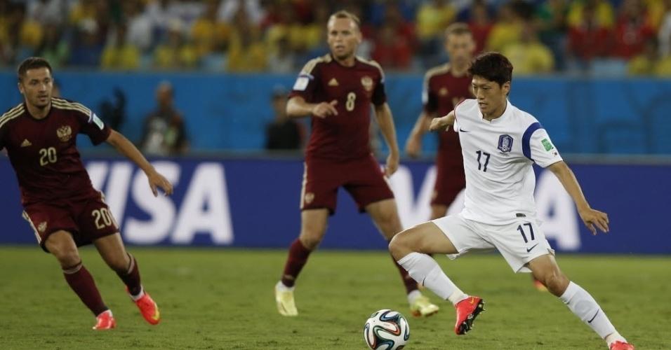 Capitão da Coreia do Sul, Lee Chung-Yong é observado pelos jogadores russos durante partida na Arena Pantanal