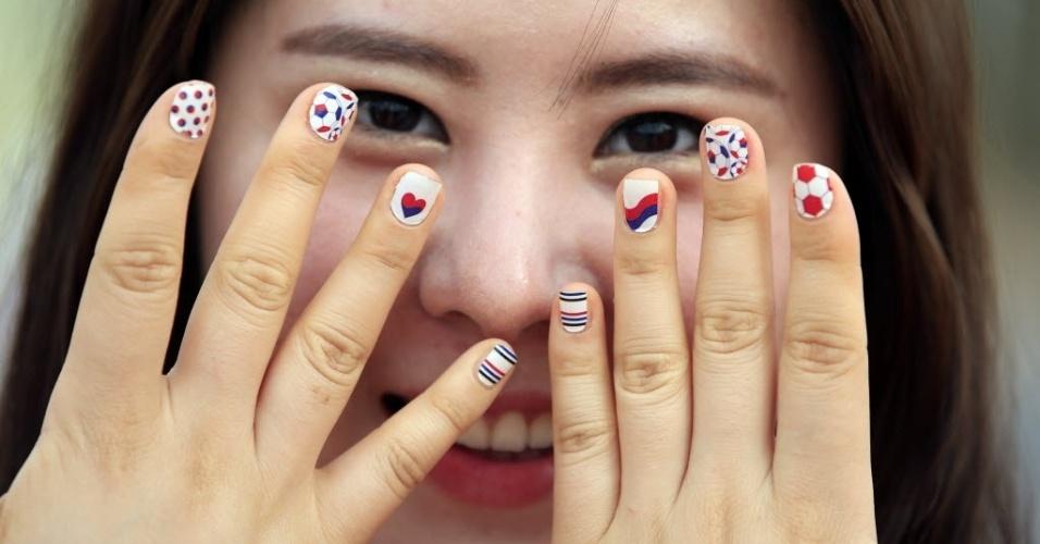 Torcedora com unhas pintadas nas cores da Coreia do Sul posa para foto antes do jogo em Cuiabá
