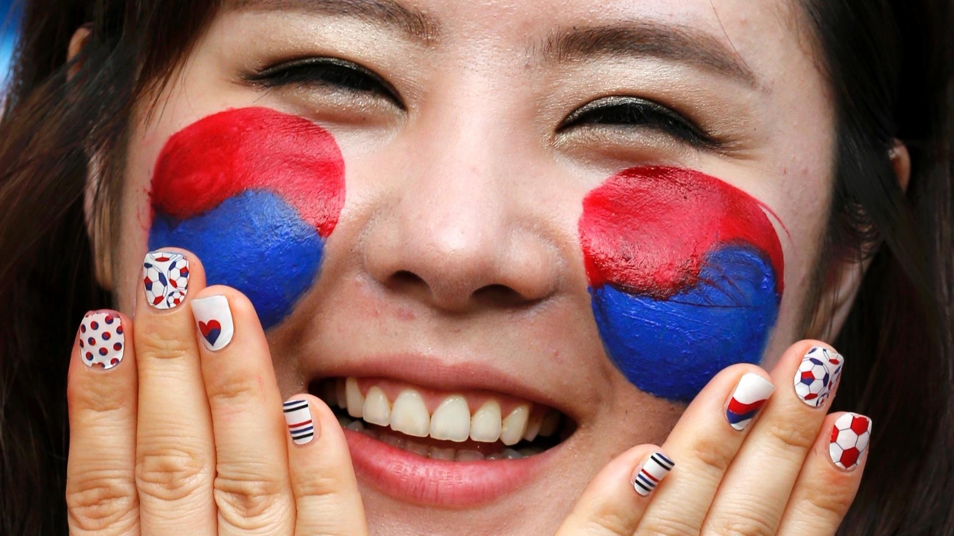 17.jun.2014 - Torcedora coreana pinta o rosto com as cores do país para a partida contra a Rússia, em Cuiabá