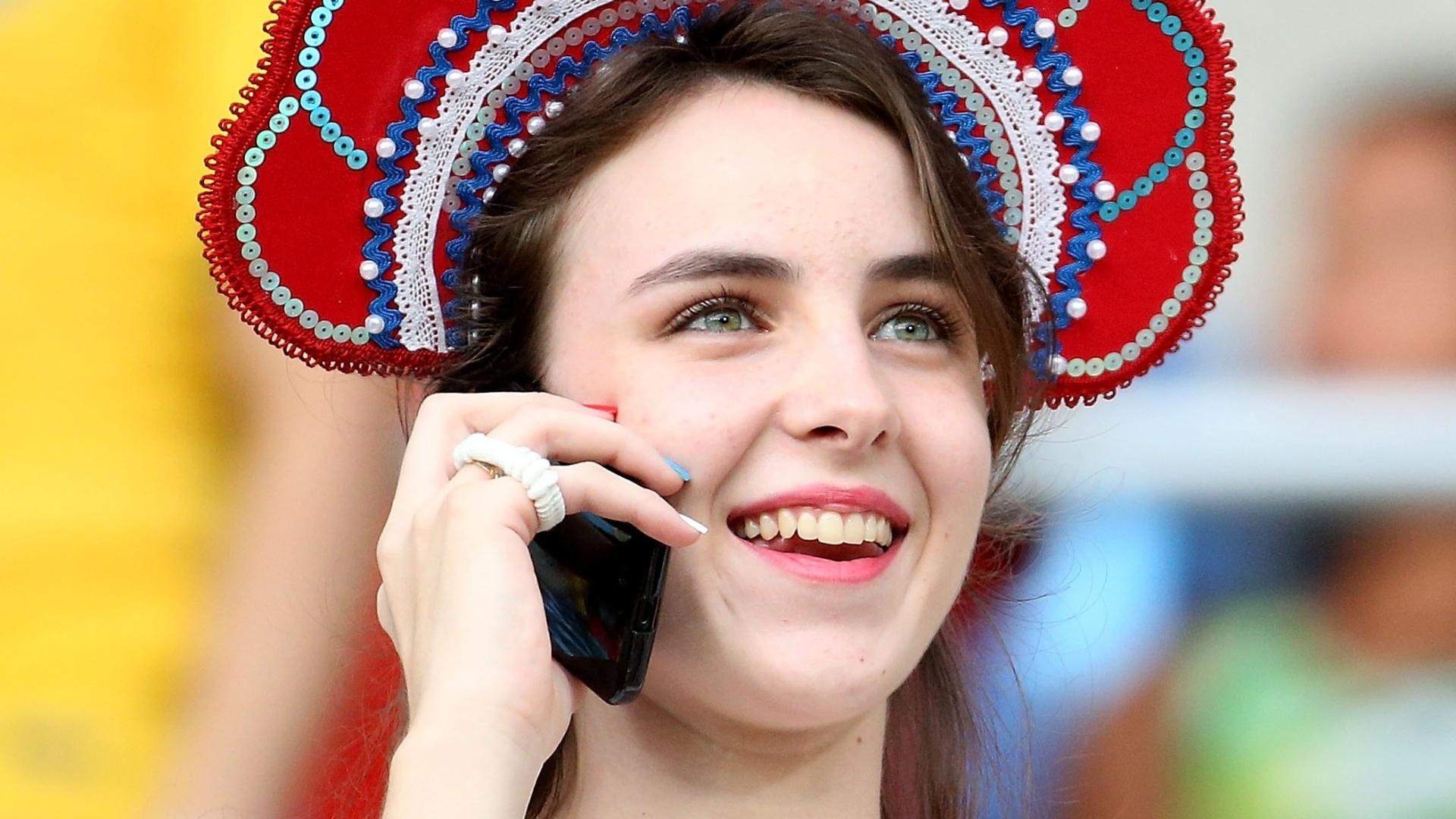 17.jun.2014 - Torcedora da Rússia fala ao telefone enquanto a equipe joga contra a Coreia do Sul, em Cuiabá