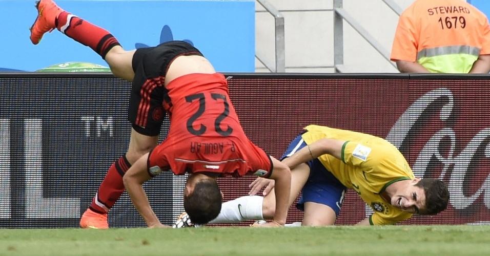 17.jun.2014 - Oscar e mexicano Paul Aguilar dividem a bola e ficam caídos no gramado do Castelão