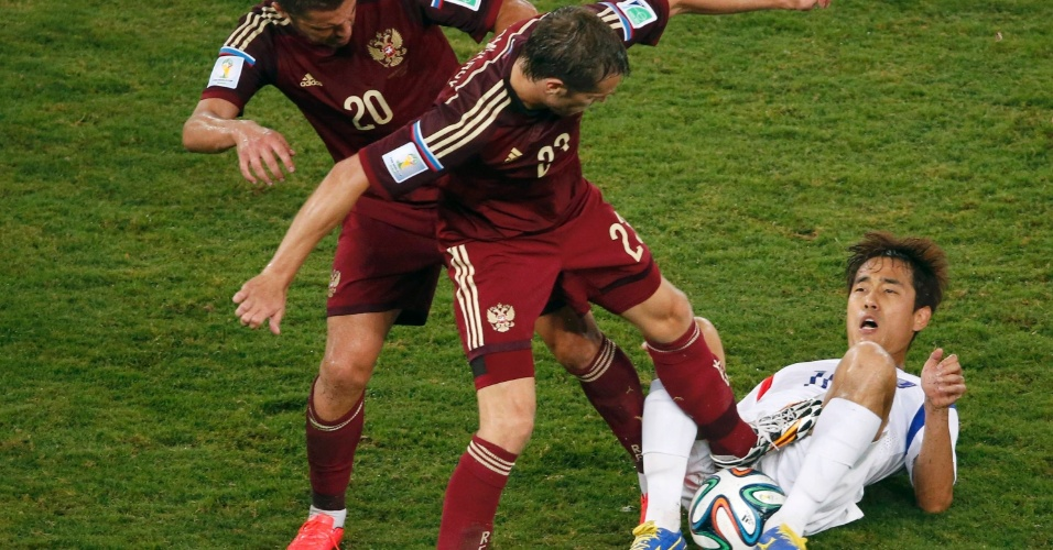 Russo Victor Faizulin and Dmitry Kombarov tentam tirar a bola do sul-coreano Park Chu-young, caído no chão