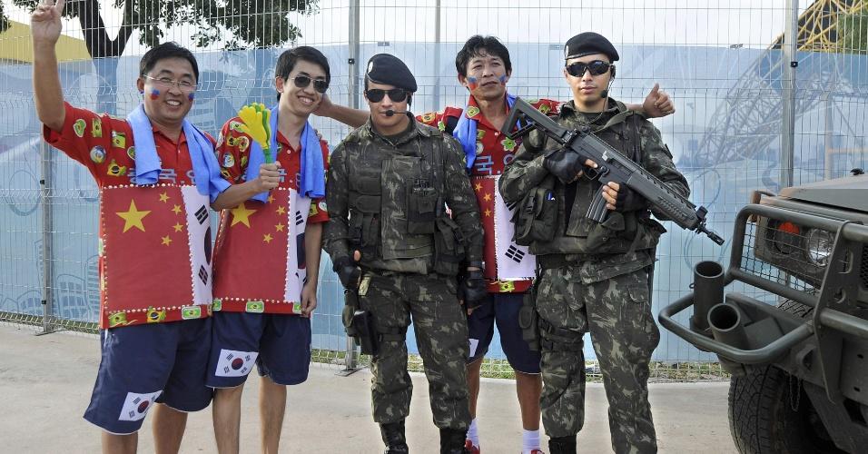 Torcedores sul-coreanos tiram fotos com homens do Exército antes de jogo entre Rússia e Coreia do Sul, na Arena Pantanal