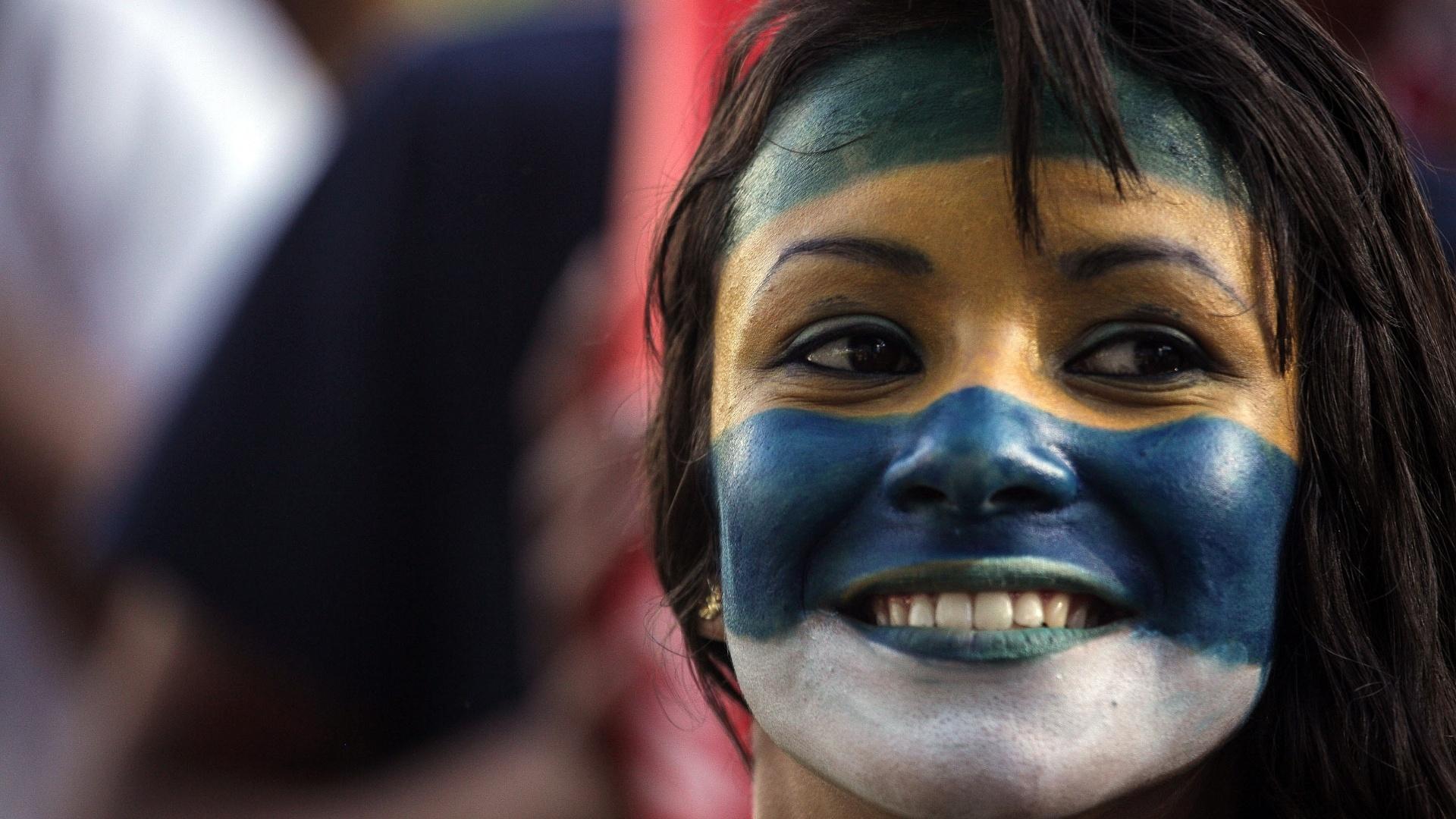 Torcedora brasileira pinta o rosto para curtir a Copa