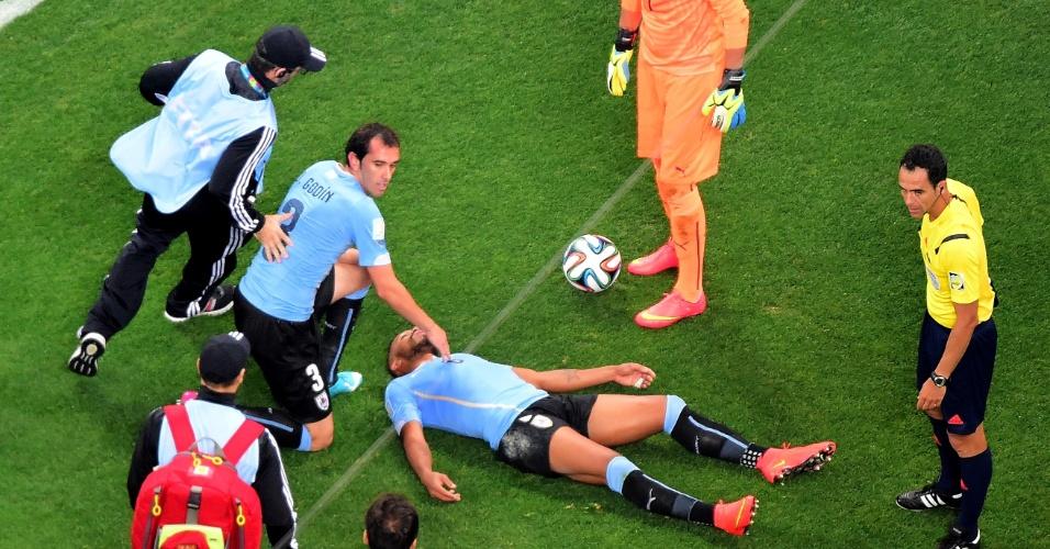 19.jun.2014 - Álvaro Pereira aguarda atendimento médico no gramado do Itaquerão após levar joelhada no rosto