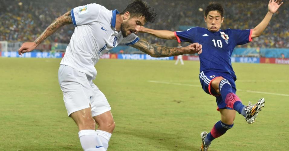 Armador da seleção japonesa, Shinji Kagawa ajuda na marcação em tentativa de passe do grego Panagiotis Kone