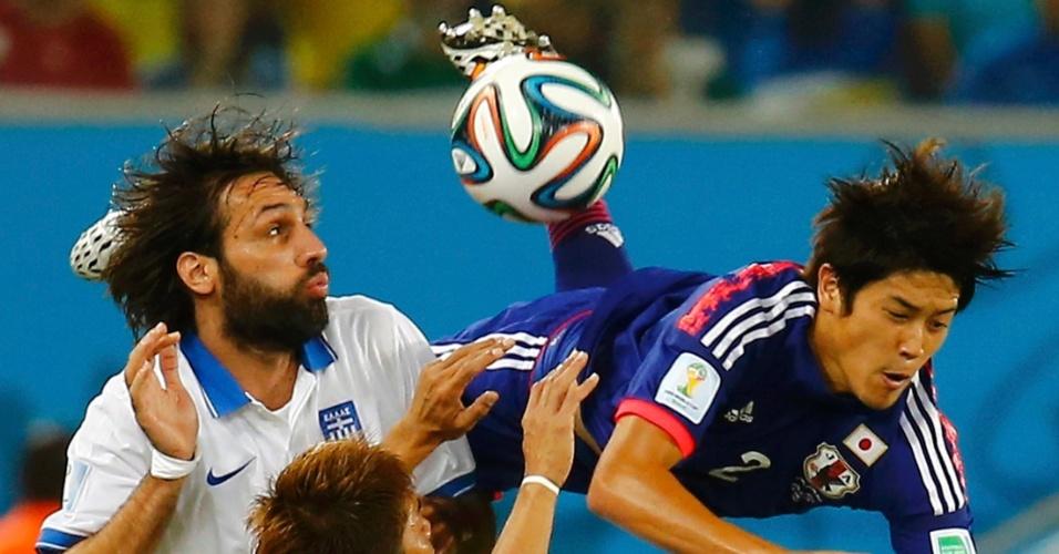 Georgios Samaras, da Grécia, observa a bola enquanto o japonês Atsuto Uchida começa a se proteger antes de cair no gramado